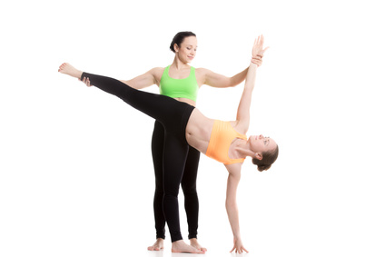 Two beautiful sporty girls practice yoga with partner, coach helps student, doing balance exercise Half Moon Pose, Ardha Chandrasana, posture therapeutic for backache