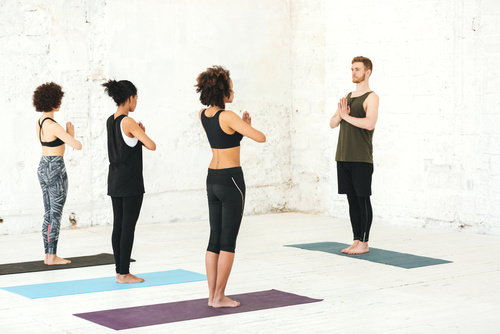 Group of multicultural women practicing yoga with male instructo